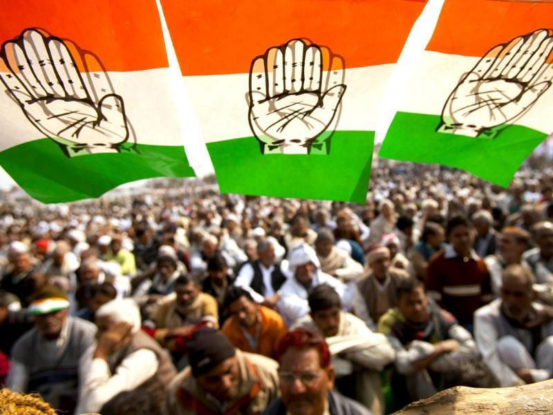 Spectators sit under a festoon of flags of the Congress party at an election rally in Meerut. AP Photo