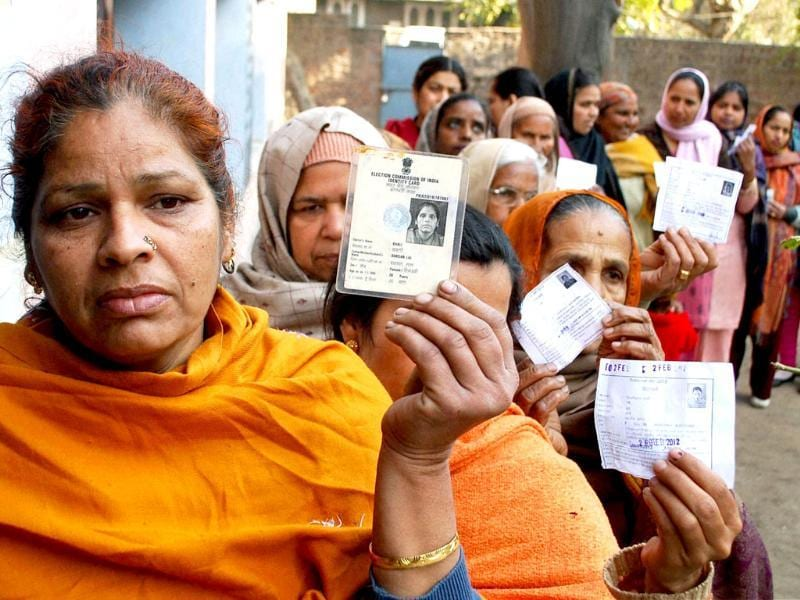 Voters show their identity cards as they wait to cast votes during re-polling at a booth in Amritsar. The Election Commission had ordered re-polling due to a fault in an EVM. PTI Photo
