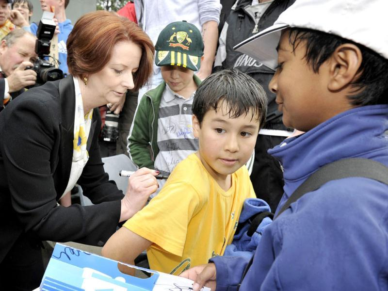 Australian prime minister Julia Gillard (L) signs a fan's shirt during the Sri Lanka V Prime Ministers XI cricket team match at Manuka Oval in Canberra. The game was abandoned due to rain. AFP PHOTO / Mark GRAHAM