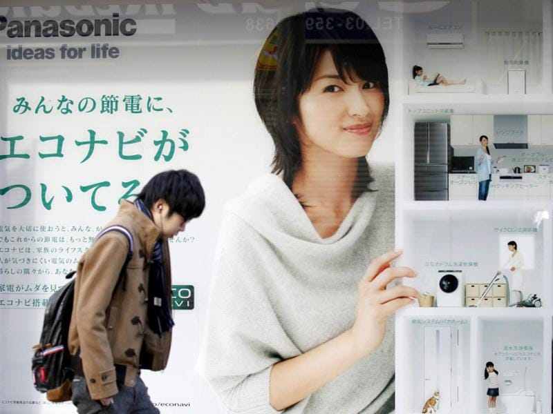 A man walks past an advertisement board of Panasonic outside an electronic shop in Tokyo. Panasonic Corp is likely to forecast a record net annual loss of more than $9.2 billion, local media reported, as it tallies the cost of trying to fix its broken TV unit and writes down its Sanyo Electric acquisition, joining a trinity of beleaguered Japanese consumer electronic giants. REUTERS/Kim Kyung-Hoon