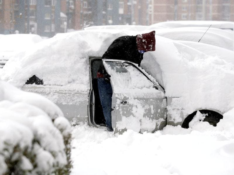 A man opens the door of his snow-covered car in Kosovo's capital Pristina. Pristina's weather office reported that snow has reached 130 cm (51 inch) in the mountain regions and 70 cm (28 inch) in other areas, and from Friday temperatures are seen falling to up to minus 20 degrees Celsius. Reuters/Hazir Reka