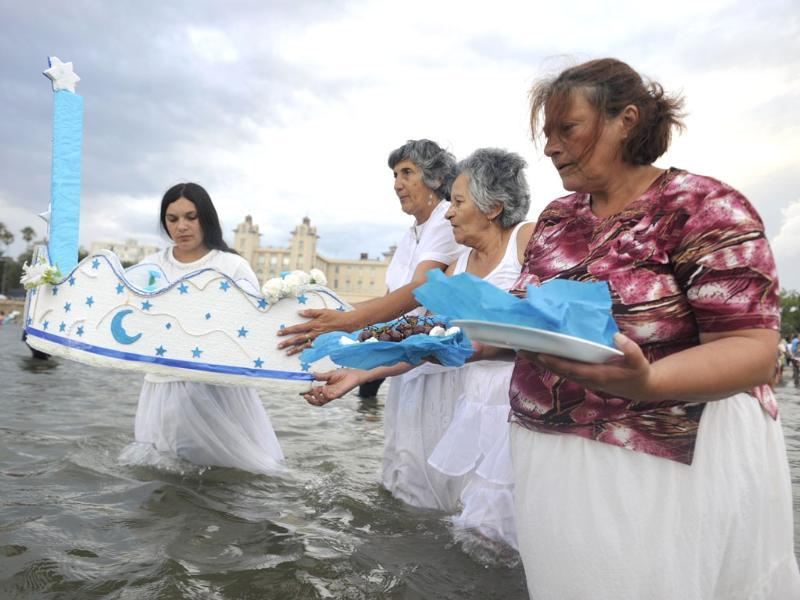 Womenan carry offering to Lemanja, the goddess of the Sea of the Afro-American religion Umbanda, during the celebration of Lemanja Day at Ramirez beach in Montevideo. AFP Photo/Pablo Porciuncula