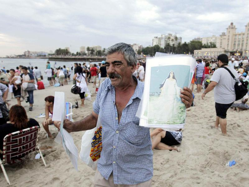 A man sells posters of the Afro-Brazilian goddess of the sea Lemanja as devotees pay tribute on Lemanja Day at Ramirez beach in Montevideo. Reuters/Andres Stapff