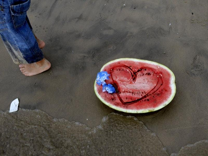 A person walks past a watermelon, placed on the beach as a tribute to Lemanja, the African goddess of the sea, in Montevideo. AP Photo/Matilde Campodonico