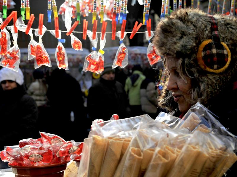 A woman protects herself from the cold wind during Saint Blas Day, as she prepares sweets blessed to protect the health of people, in Pamplona, northern Spain, Friday. (AP Photo/Alvaro Barrientos)