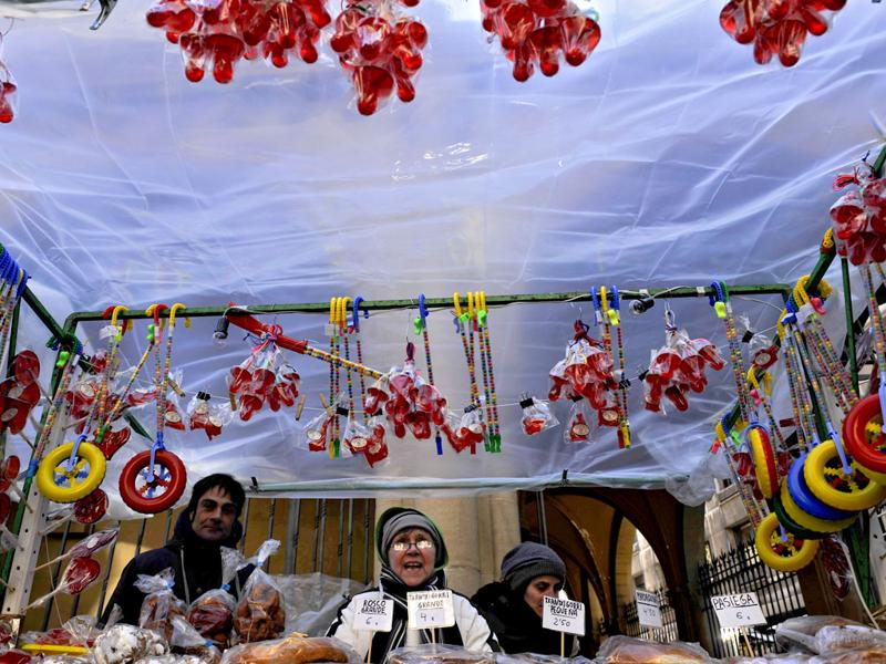 People protects thenself from the cold wind during Saint Blas Day, a day when people buy sweets blessed to protect their health, in Pamplona, northern Spain. (AP Photo/Alvaro Barrientos)