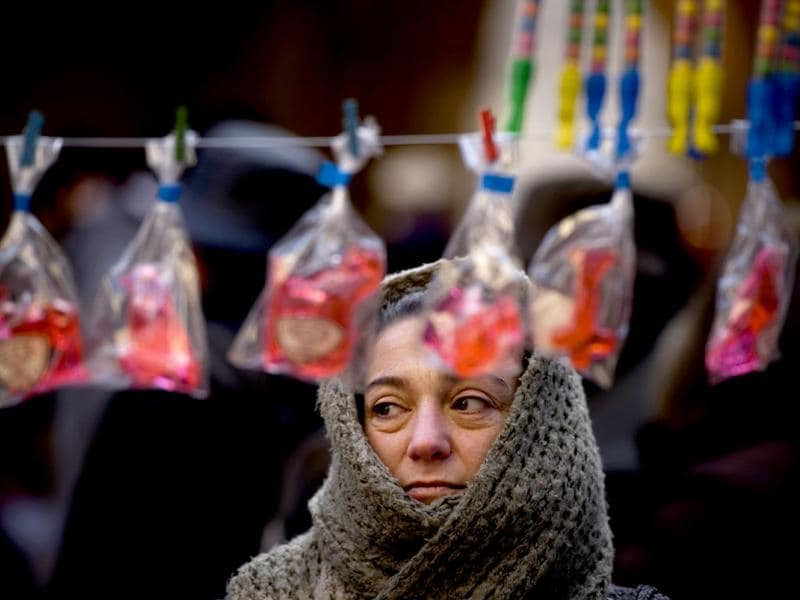 A woman protects herself from the cold wind during Saint Blas Day, a day when people buy sweets blessed to protect their health, in Pamplona, northern Spain. (AP Photo/Alvaro Barrientos)