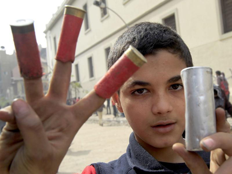 An Egyptian boy holds empty bullet casings and a tear gas canister fired by riot policemen during clashes near the interior ministry in downtown Cairo. AFP/Mahmud Hams