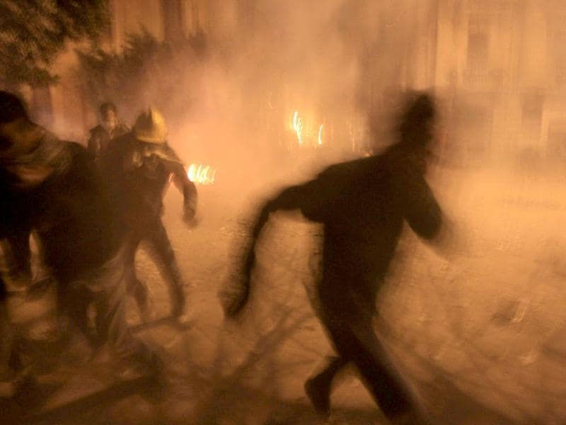 Egyptian protesters run for cover from the teargas fired by riot police near the interior ministry in downtown Cairo. AFP/Khaled Desouki