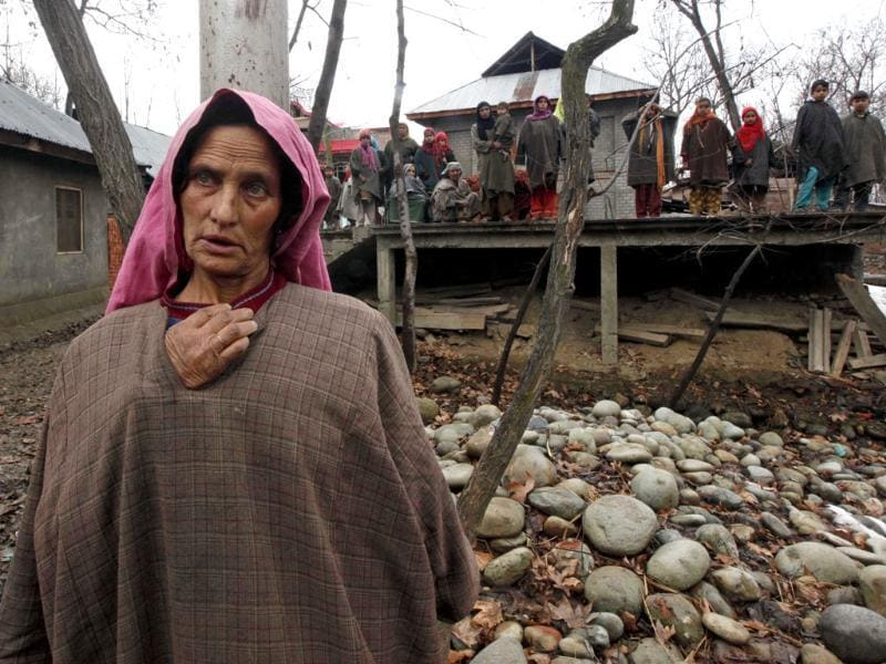 A Kashmiri village woman stands near the site of a gunbattle in Woodder village, some 41 kilometers south of Srinagar. AP Photo