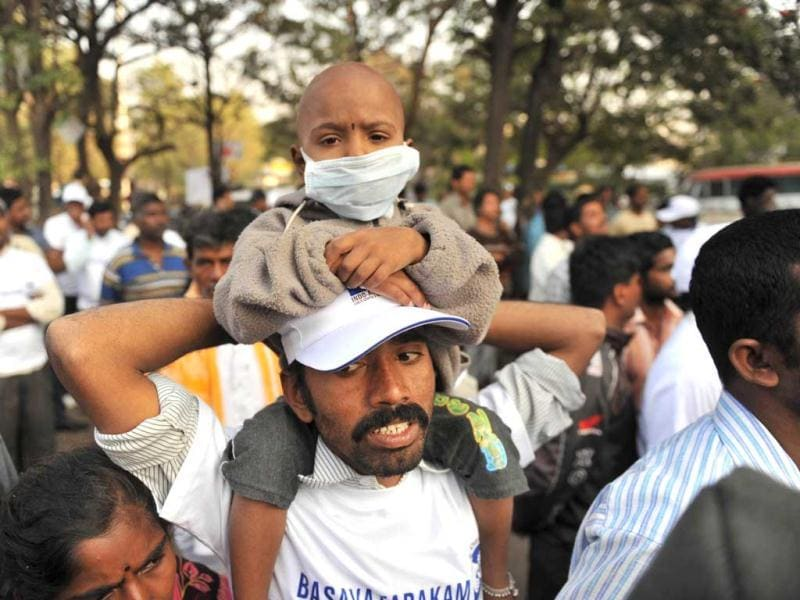 Vaddi Akhila, 5, who is currently undergoing outpatient cancer treatment at the Basavatarakam Indo-American Cancer Hospital and Research Institute, sits over the shoulders of his father during a cancer awareness walk in Hyderabad during World Cancer Day. AFP/Noah Seelam