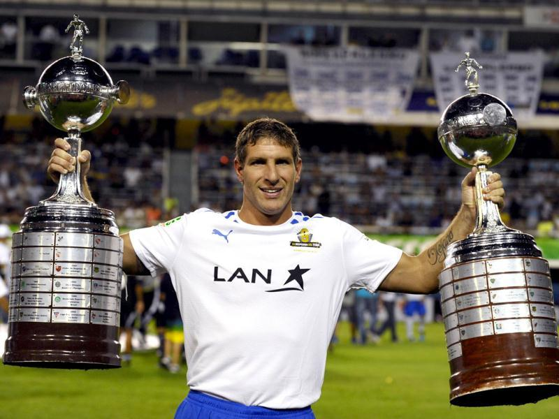 Former Boca Juniors footballer Martin Palermo holds Boca Juniors' two Copa Libertadores trophies, before the start of his farewell football match, at La Bombonera stadium in Buenos Aires. AFP/ Alejandro Pagni
