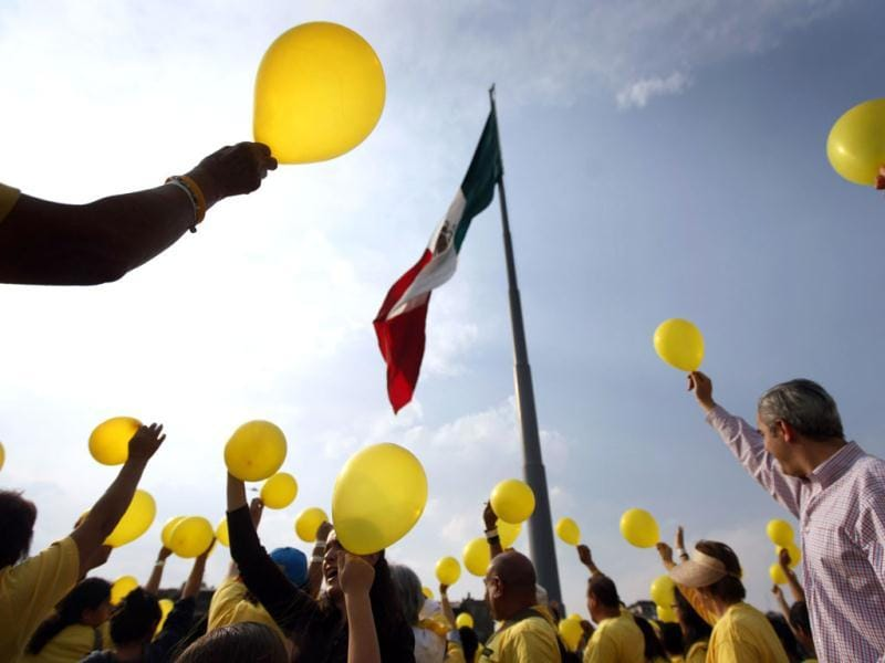 People hold up yellow balloons as they commemorate World Cancer Day at Zocalo Square in Mexico City. 5,298 people formed a human chain during the event, according to the organisers. Reuters/Edgard Garrido