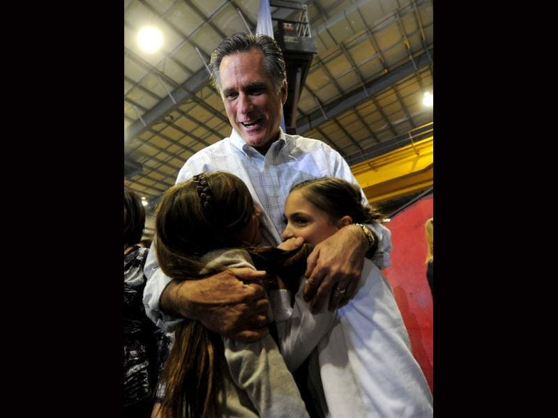 US Republican presidential hopeful Mitt Romney hugs grandaughters (L-R) Grace and Chloe during a campaign rally at Colorado Spring Fabrication in Colorado Springs, Colorado. AFP/Emmanuel Dunand