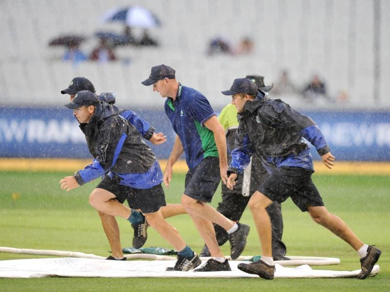 MCG ground staff race to place covers on the cricket field as rain stops play in the India verses Australia One Day international match at the MCG in Melbourne. (AP Photo/Mal Fairclough)