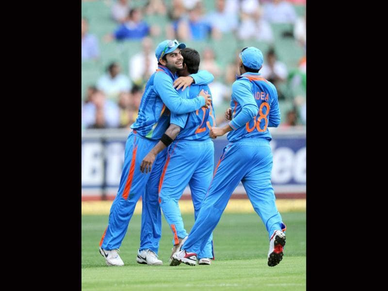 India's Ranganath Vinay Kumar, center, celebrates with a teammates after taking the wicket of Australia's ,during their one cay international cricket match at the MCG in Melbourne. (AP Photo/Mal Fairclough)