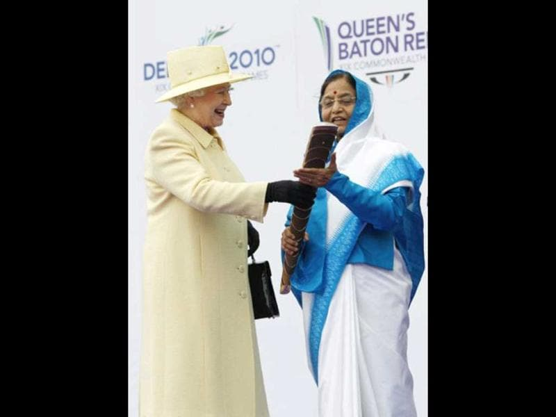 Queen Elizabeth II (L) hands a ceremonial relay baton to President Pratibha Patil during the the launch of the XIX Commonwealth Games Queen's Baton Relay for Delhi 2010, at Buckingham Palace in London, on October 29, 2009. File Photo. AFP Photo/Suzanne Plunket