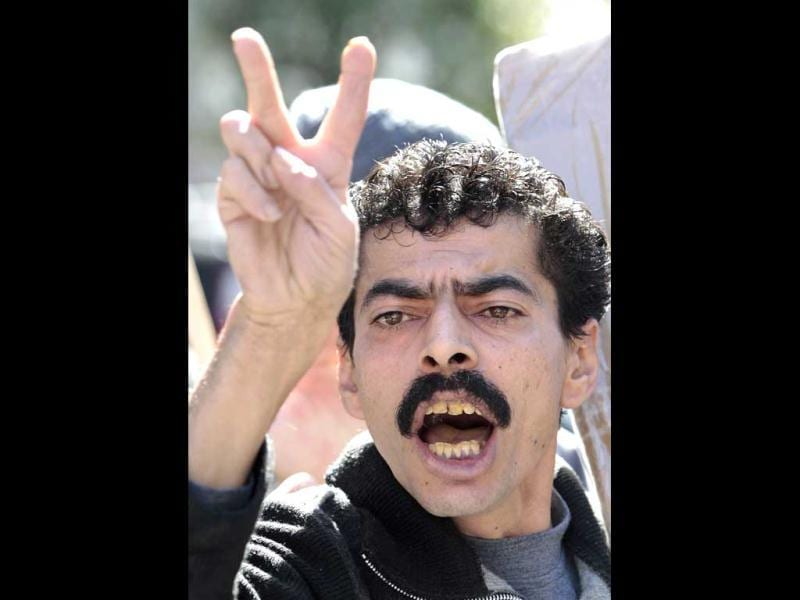An anti-Syrian regime protester and supporter of the Islamic group Jamaa Islamiya, who are opposed to Syrian President Bashar Assad, flashes the victory sign as he shouts slogans during a demonstration where a number of Assad supporters were also protesting, in front the Russian embassy, in Beirut, Lebanon (AP Photo)