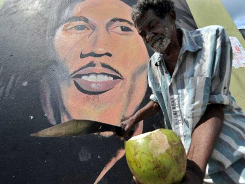 A vendor prepares a coconut for a customer in front of a mural of late musician Bob Marley in Kingston. Marley, who was born in 1945 and died in 1981, remains the most widely known and revered performer of reggae music and is also credited for helping spread Jamaican music to a worldwide audience. (AFP Photo)