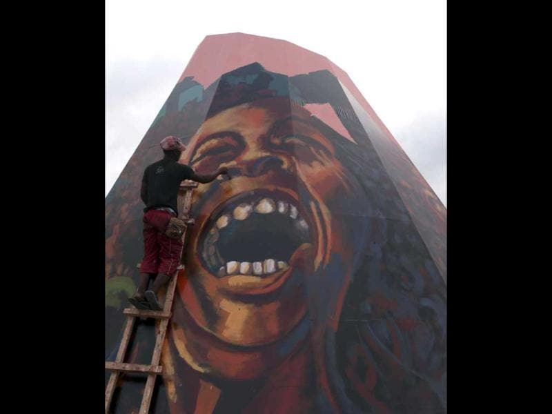 A worker paints a picture of Jamaican musician Bob Marley in a square along a street in Bata. February 6, 2012 marks the 67th birth anniversary of the reggae star. (Reuters)