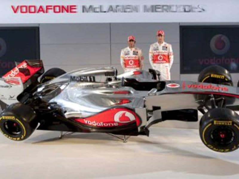 In a handout picture released by Vodaphone McLaren Mercedes, drivers Lewis Hamilton (L) and Jenson Button (R) of Britain pose behind the newly unveiled McLaren MP4-27 Formula One car during McLaren's 2012 technical launch for the new season in Woking. AFP photo/Vodafone Mclaren Mercedes