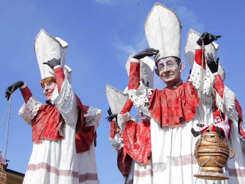 A carnival float showing US President Barack Obama, German Chancellor Angela Merkel (L), Italian prime minister Mario Monti and French President Nikolas Sarkozy (R) dressed as ecclesiastes parade during the carnival in Viareggio. AFP PHOTO/Fabio Muzzi