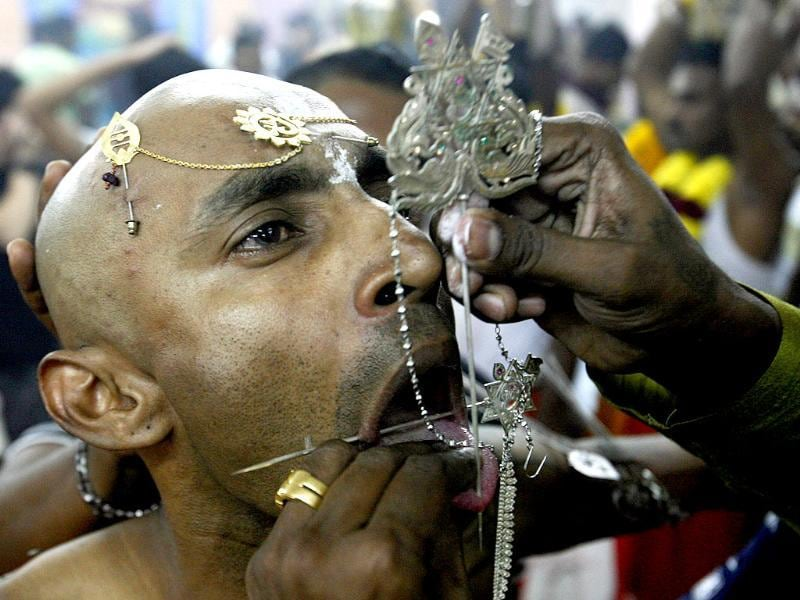 Devotee Guna, 37, has his tongue pierced during the Thaipusam festival in Singapore. Thaipusam, a Hindu festival observed on the day of the full moon during the Tamil month of Thai, is celebrated in honour of Lord Murugan. REUTERS/Edgar Su