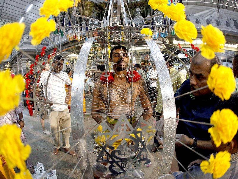 Relatives do a final check on devotee R Balasubramaniam's Kavadi during the Thaipusam festival in Singapore. Thaipusam, a Hindu festival observed on the day of the full moon during the Tamil month of Thai, is celebrated in honour of Lord Murugan. A Kavadi is the physical burden carried by the devotee during their worship of Lord Murugan and represents the devotee's call for help from the god. REUTERS/Edgar Su