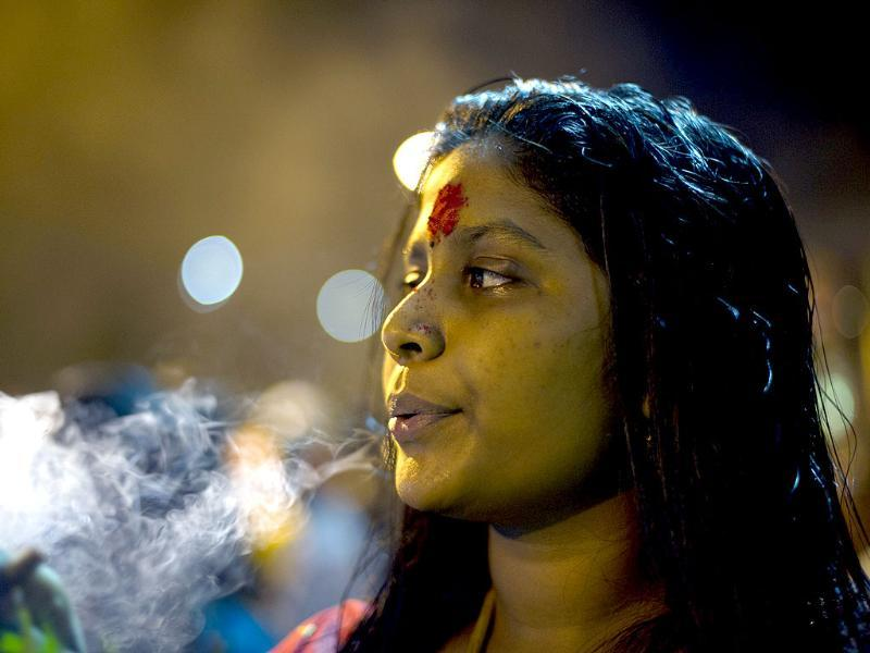 A Hindu devotee takes a puff on a cigar near the Batu Caves during the Thaipusam Festival on the outskirts of Kuala Lumpur. The Hindu festival of Thaipusam, which commemorates the day when Goddess Pavarthi gave her son Lord Muruga an invincible lance with which he destroyed evil demons, is celebrated by some two million ethnic Indians in Malaysia and Singapore. AFP PHOTO / Saeed KHAN