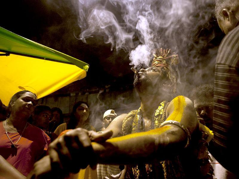 A Hindu devotee takes a puff on a cigar while getting ready for the pilgrimage at the Batu Caves for their religious rites before sunrise during the Thaipusam Festival on the outskirts of Kuala Lumpur. The Hindu festival of Thaipusam, which commemorates the day when Goddess Pavarthi gave her son Lord Muruga an invincible lance with which he destroyed evil demons, is celebrated by some two million ethnic Indians in Malaysia and Singapore. AFP PHOTO / Saeed KHAN