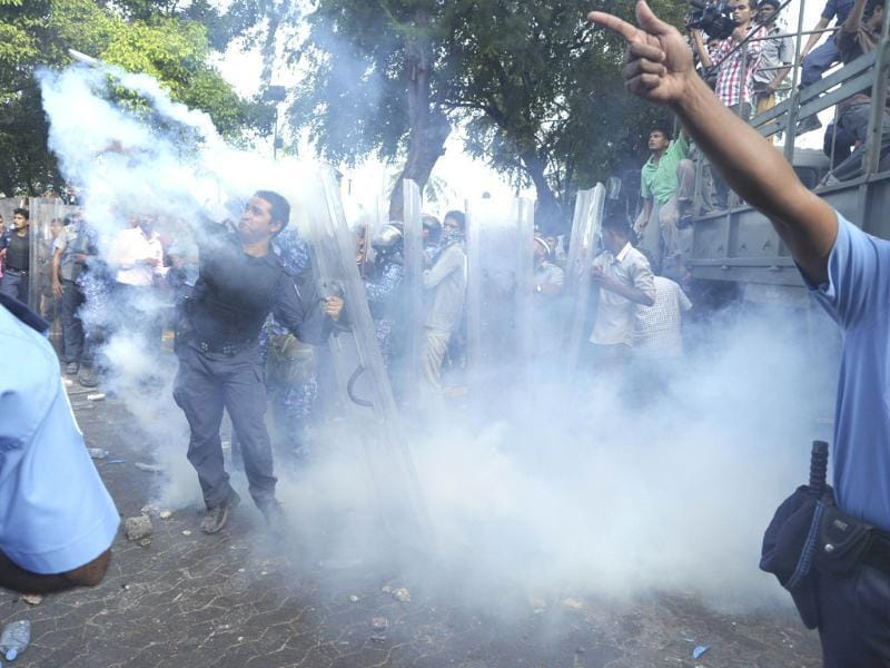 In this handout photograph provided by Haveeru News Service, mutinying Maldivian police are seen amid a cloud of tear gas as they confront the military in Male. A group of policemen in the Maldives disobeyed orders and joined anti-government protesters in what the president's office described as a
