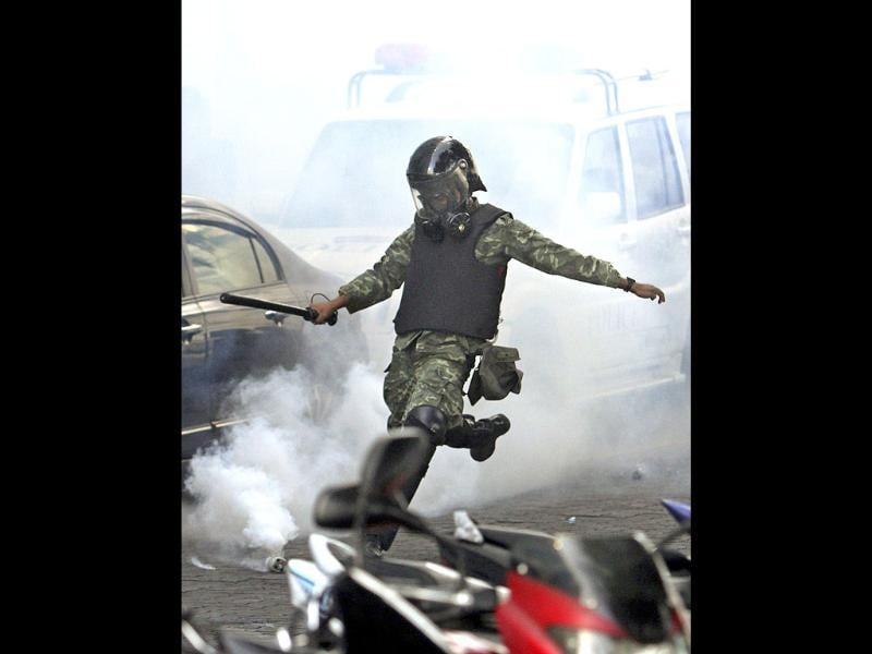 A Maldives soldier kicks a tear gas canister towards police during a clash in Male, Maldives. The first democratically elected president Mohamed Nasheed of Maldives resigned today after police joined the protesters and then clashed with soldiers amid protests over his controversial arrest of a top judge. (AP Photo/Sinan Hussain)