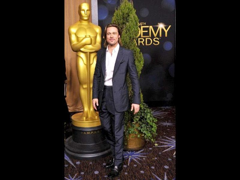 Best Actor nominee Brad Pitt poses next to the Oscar statuette.