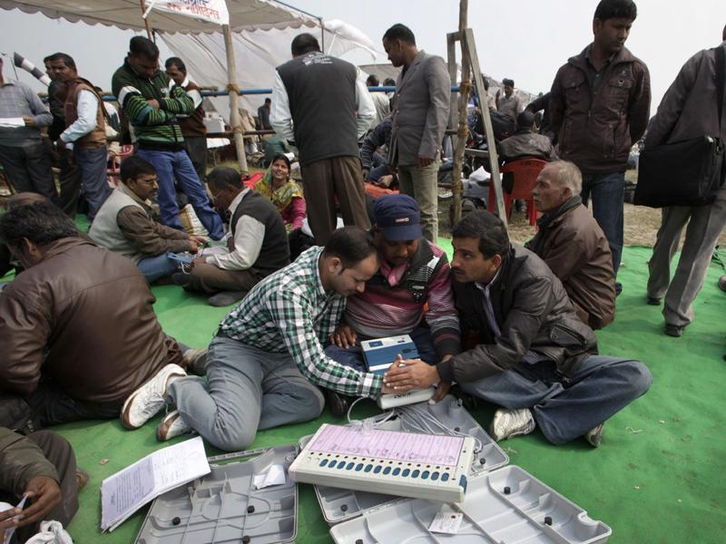 Polling officers check and learn the workings of electronic voting machines before leaving for their respective polling booths, in Ayodhya. (AP Photo/Manish Swarup)