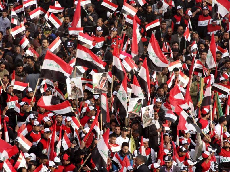 Supporters of anti-US Shi'ite cleric Moqtada al-Sadr wave Iraqi flags during a rally in Baghdad. (Reuters/Kareem Raheem)