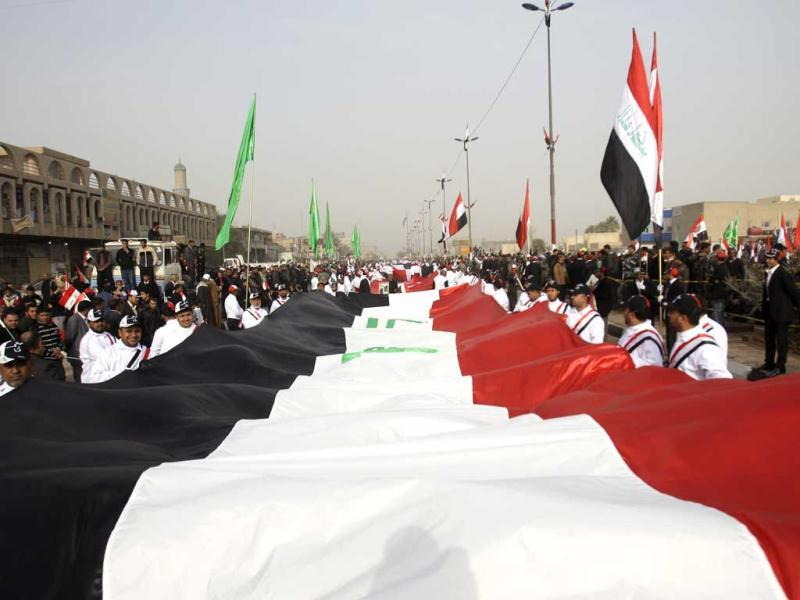 Followers of Shiite cleric Muqtada al-Sadr carry a huge Iraqi flag as they celebrate the US withdrawal in the Shiite stronghold of Sadr City in Baghdad. (AP Photo/Khalid Mohammed)