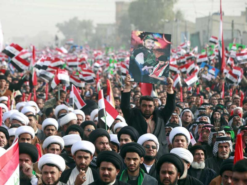 Followers of Shiite cleric Muqtada al-Sadr, depicted in poster being held, chant anti-US slogans in the Shiite stronghold of Sadr City in Baghdad. (AP Photo/Karim Kadim)