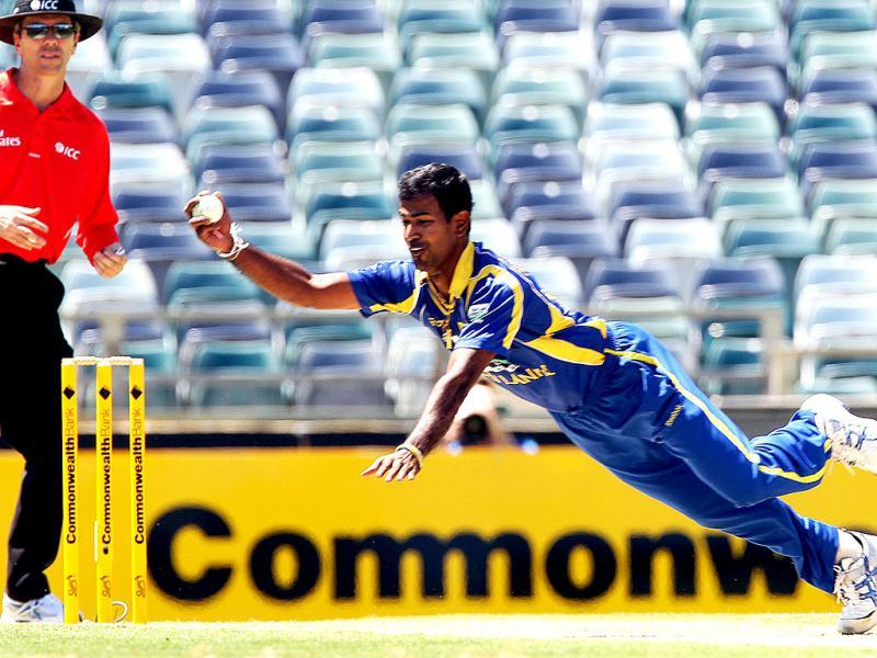 Sri Lankan bowler Nuwan Kulasekara catches the ball to bowl Australian batsman Mike Hussey (unseen) during the Tri Nations ODI Cricket Series match in Perth. AFP