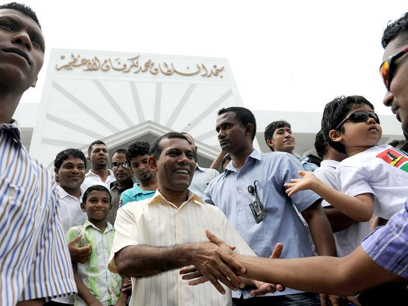 Former Maldives president Mohamed Nasheed (C) greets people after Friday prayers in Male. Nasheed demanded fresh elections after being ousted in what he called a coup d'etat. AFP photo