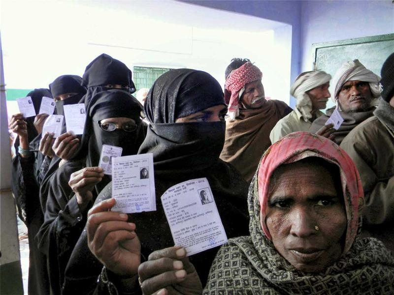 Women show their identity cards as they wait at a polling station to cast their votes during the second phase of UP assembly polls in Azamgarh. PTI Photo