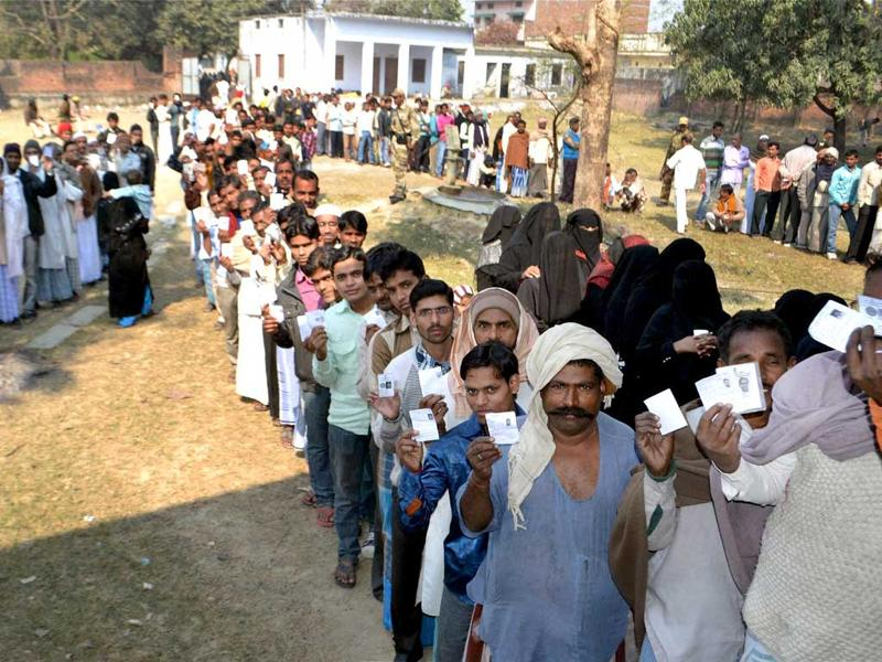 Voters show their identity cards as they wait at a polling station to cast their votes during the second phase of UP assembly polls in Azamgarh . PTI Photo