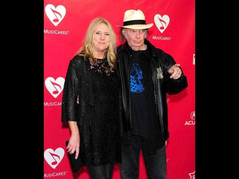 Neil Young gestures while posing with his wife Pegi.