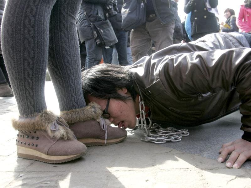 A man with a chain around his neck licks the shoes of a woman on a sidewalk during a performance in Wuhan, Hubei province. Four artists and art students presented the performance as part of a demonstration calling for equality for men and women, local media reported. Picture taken on February 8, 2012. Reuters/Stringer