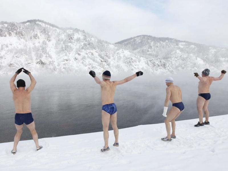 Members of a local winter swimming club warm up on the bank of the Yenisei River before going for a swim in an air temperature around minus 25 degree Celsius (minus 13 Fahrenheit) in the town of Divnogorsk, some 38 km (24 miles) south of the Siberian city of Krasnoyarsk. Picture taken on February 3, 2012. Reuters/Ilya Naymushin