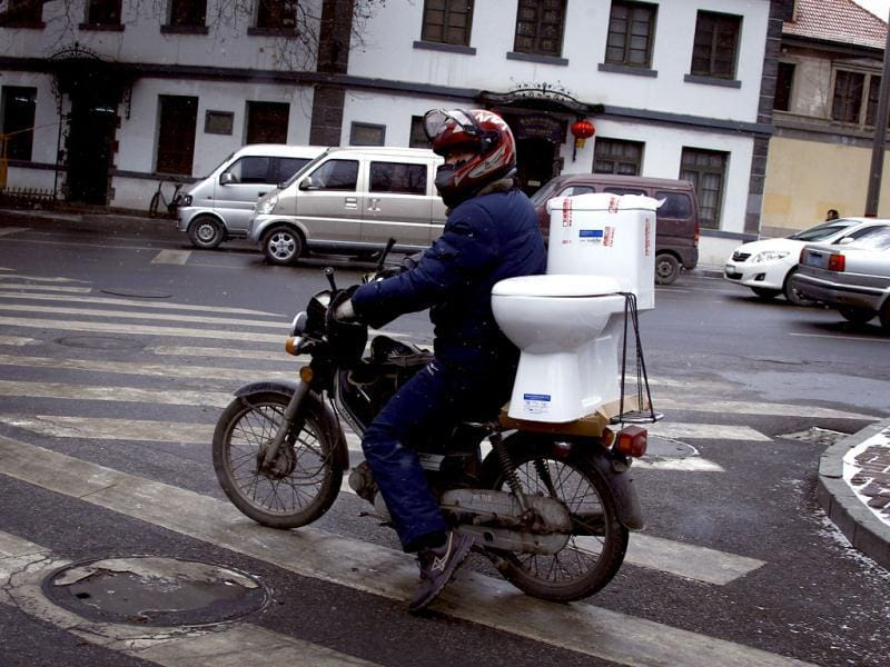 A man rides a motorbike with a toilet strapped on the back of the seat along a street in the southern Chinese city of Yantai, Shandong Province. Picture taken on February 7, 2012. Reuters/David Gra