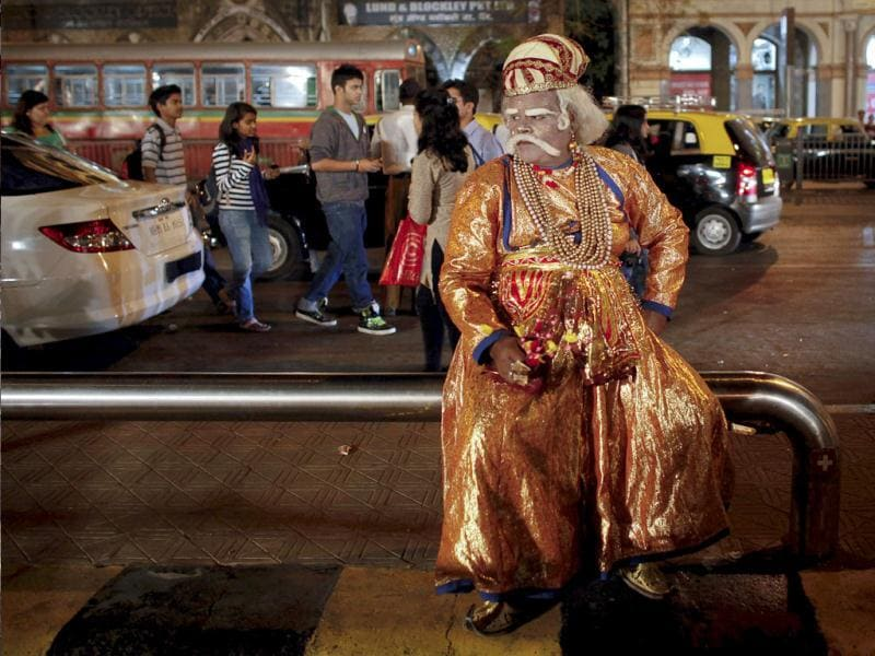 An artist dressed as Mughal emperor Akbar sits along the roadside in Mumbai. Picture taken on February 9, 2012. Reuters/Danish Siddiqui