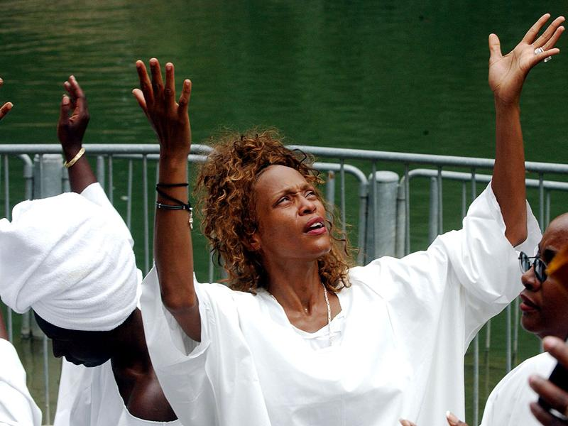 American pop diva Whitney Houston emerges from the waters of the River Jordan near the Sea of Galilee during a Holy Land pilgrimage, in this file photo taken May 29, 2003. REUTERS/Ygal Levi