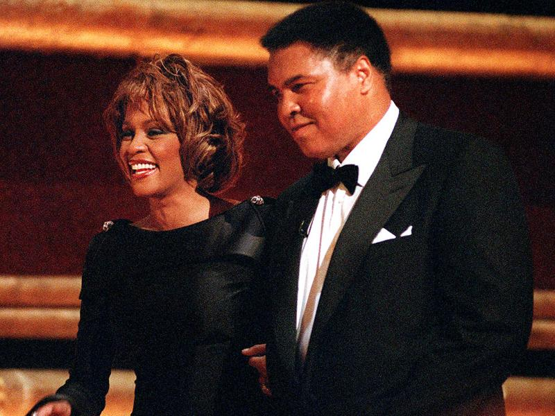 In this Oct 21, 1998 file photo, World Heavyweight Boxing Champion Muhammad Ali is greeted by singer Whitney Houston as he arrives on stage at New York's Radio City Music Hall to accept a GQ