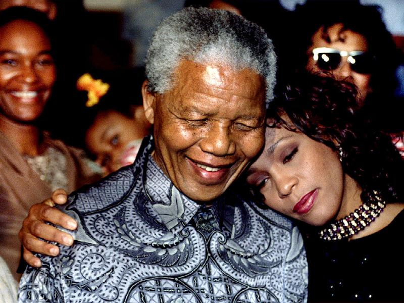 Former South African president Nelson Mandela and American pop star Whitney Houston smile for photographers in Johannesburg. (Reuters file photo)