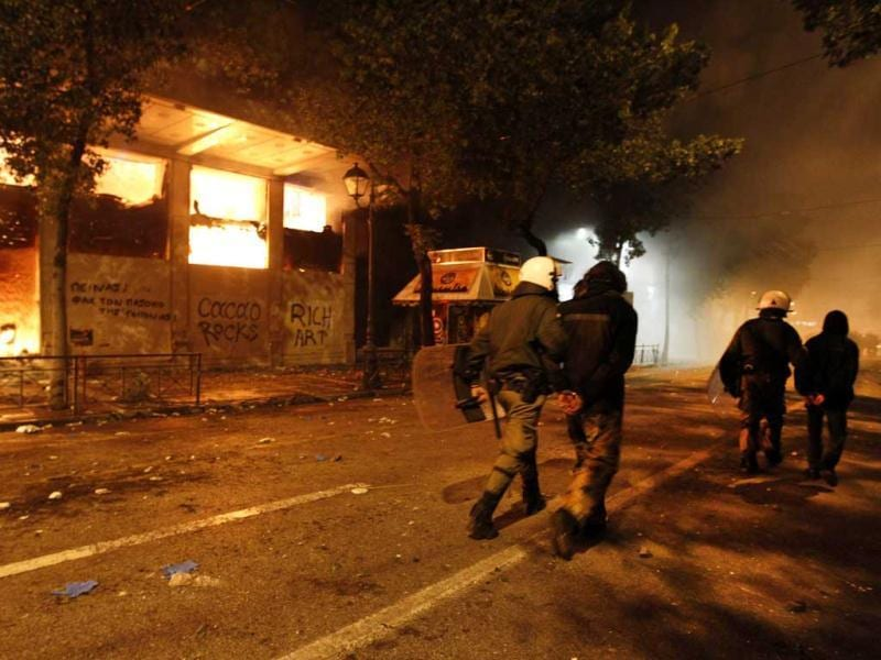 Riot police move detained protesters past a burning historic building during violent protests in central Athens. Historic cinemas, cafes and shops went up in flames in central Athens on Sunday as black-masked protesters fought Greek police outside parliament, while inside lawmakers looked set to defy the public rage by endorsing a new EU/IMF austerity deal. (Reuters)